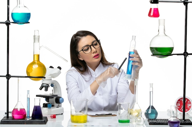 Front view female chemist in white medical suit holding flask with solution white background science virus covid- pandemic lab