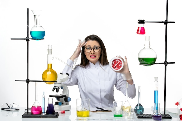 Front view female chemist in white medical suit holding red clocks on white background science virus covid- pandemic lab