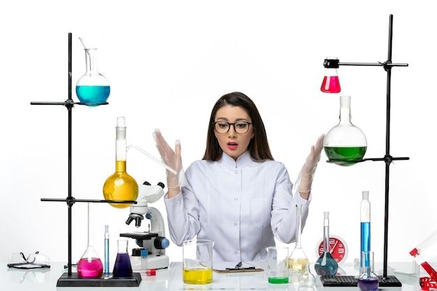 Chimico femminile di vista frontale in vestito medico bianco appena seduto con soluzioni su sfondo bianco chiaro scienza covid virus di laboratorio pandemico