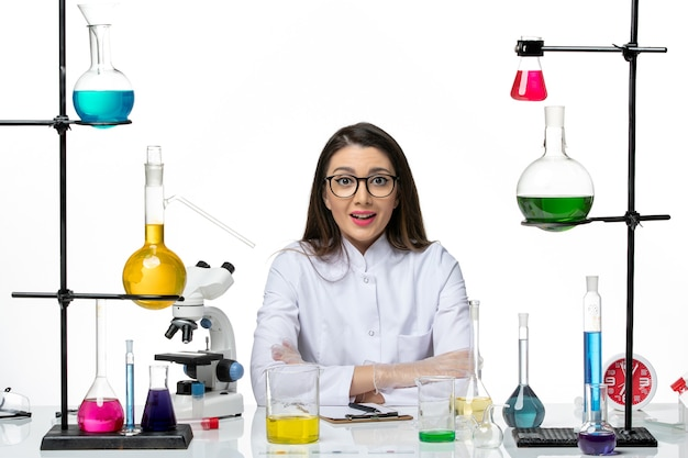 Front view female chemist in white medical suit just sitting with solutions on light white background science virus covid- pandemic lab