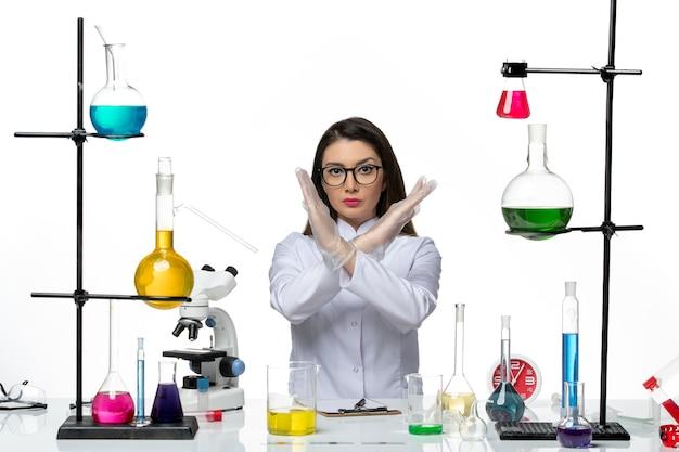 Farmacia femminile di vista frontale in vestito medico bianco appena seduto con soluzioni che mostrano il segno di divieto su sfondo bianco virus di laboratorio pandemico di scienza covid