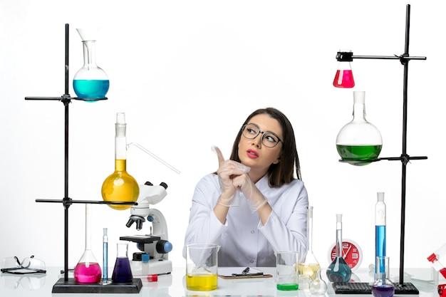 Farmacia femminile di vista frontale in vestito medico bianco appena seduto con soluzioni pensando su sfondo bianco scienza covid- laboratorio virus pandemico