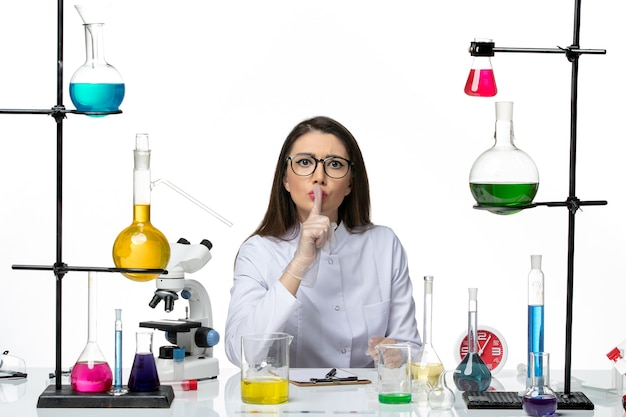 Front view female chemist in white medical suit just sitting with solutions on white background science pandemic lab virus covid