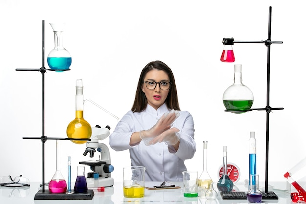 Front view female chemist in white medical suit just sitting with solutions on white desk covid- science pandemic lab virus
