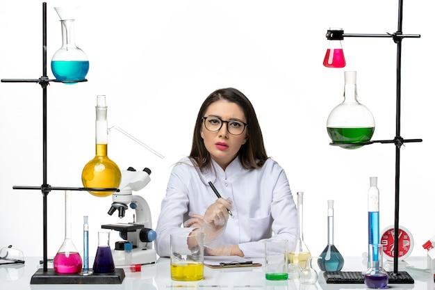 Front view female chemist in white medical suit just sitting with solutions writing notes on white background science virus covid- pandemic lab