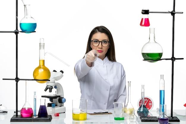 Chimico femminile di vista frontale in vestito medico bianco che si siede appena con le soluzioni che scrivono sul covid del virus del laboratorio di pandemia di scienza del fondo bianco