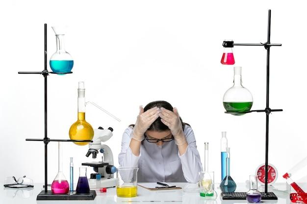 Chimico femminile di vista frontale in vestito medico bianco che si siede e che si sente stanco su scienza pandemica covid del virus del laboratorio del fondo bianco