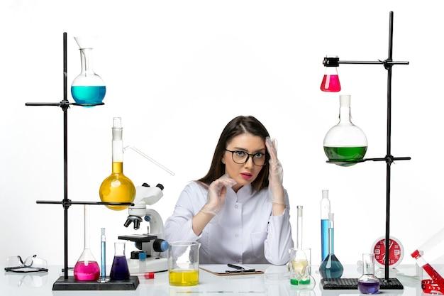 Chimico femminile di vista frontale in vestito medico bianco che si siede sulla scienza pandemica covid del virus del laboratorio del fondo bianco chiaro