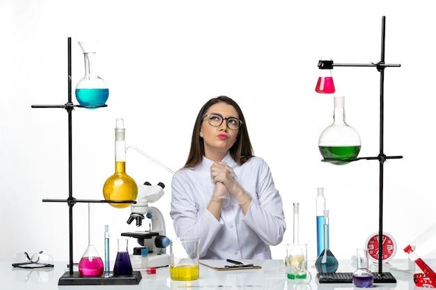Chimico femminile di vista frontale in vestito medico bianco che si siede e che pensa su pandemia di covid del virus di scienza del laboratorio del fondo bianco