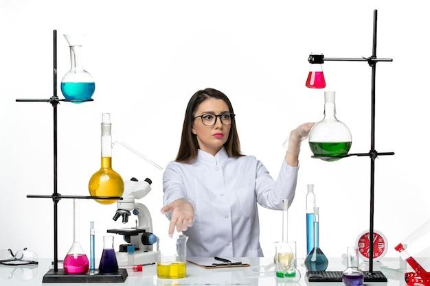 Chimico femminile di vista frontale in vestito medico bianco che si siede sulla scienza pandemica covid del virus del laboratorio del fondo bianco