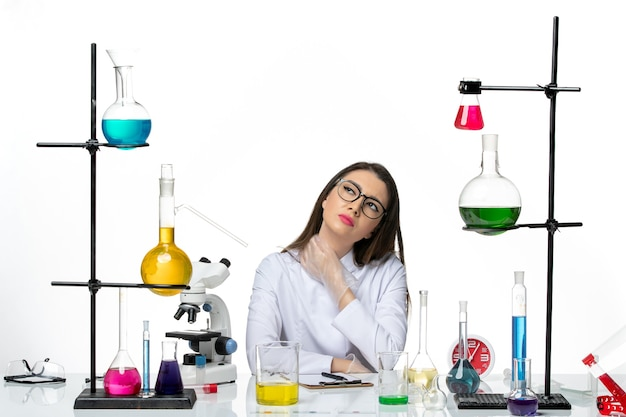 Front view female chemist in white medical suit sitting with different solutions on the white background science pandemic virus covid lab