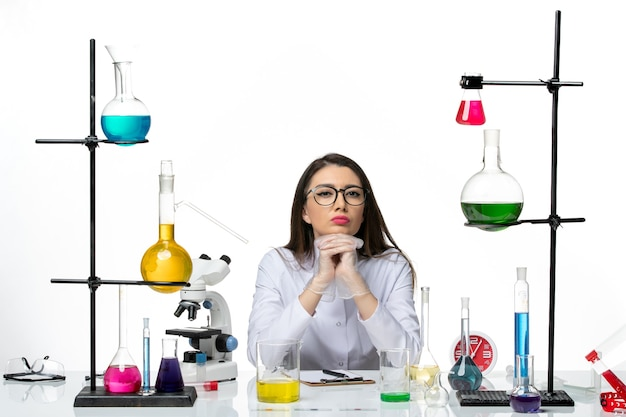 Front view female chemist in white medical suit sitting with different solutions on white background science virus covid pandemic lab