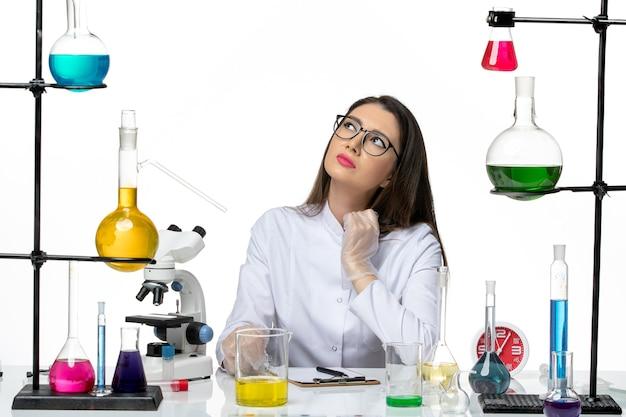 Chimico femminile di vista frontale in vestito medico bianco che si siede con le soluzioni sul laboratorio covid del virus pandemico di scienza sfondo bianco chiaro