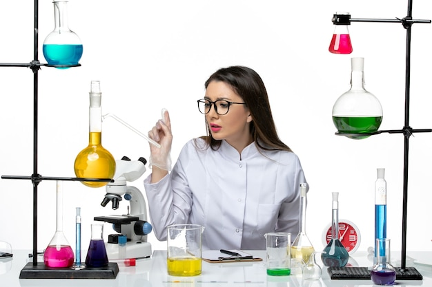 Front view female chemist in white medical suit sitting with solutions on light white background science pandemic virus covid lab