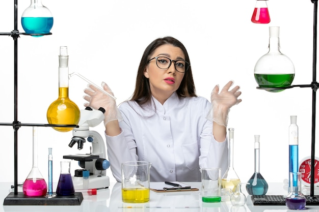 Front view female chemist in white medical suit sitting with solutions on light white background science virus covid- pandemic lab