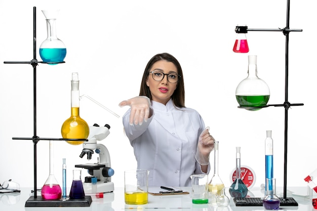 Front view female chemist in white medical suit sitting with solutions on a white background science pandemic virus covid lab