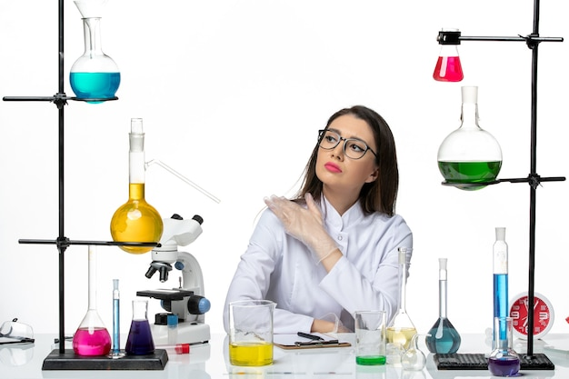 Front view female chemist in white medical suit sitting with solutions on a white background science virus covid- pandemic lab
