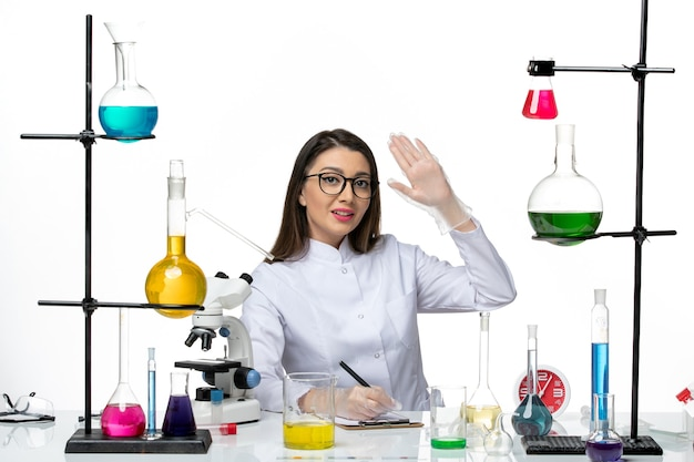 Front view female chemist in white medical suit sitting with solutions writing notes on white background science pandemic lab virus covid