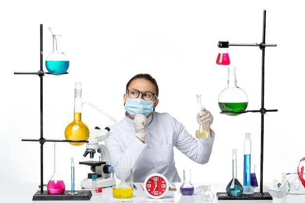 Chimico femminile di vista frontale in vestito medico bianco con la soluzione della tenuta della maschera che pensa sulla spruzzata covid del virus del laboratorio del chimico del fondo bianco