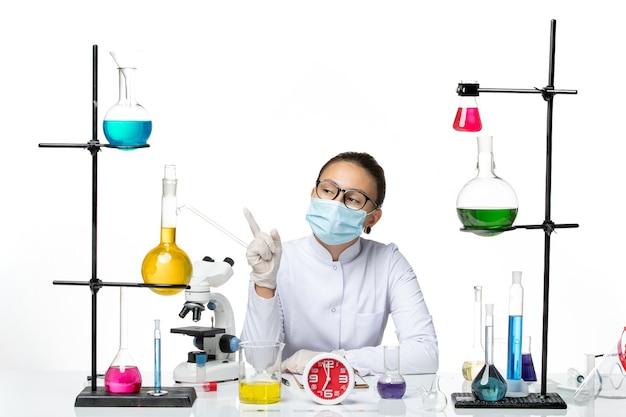 Chimico femminile di vista frontale in vestito medico bianco con la maschera che si siede e che pensa sul laboratorio bianco della spruzzata del covid del virus del chimico del fondo