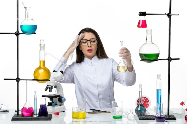 Front view female chemist in white medical suit working with solutions on the white background covid- science pandemic lab virus