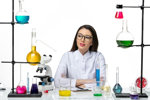 Front view female chemist in white medical suit working and writing notes on light white background science virus covid- pandemic lab