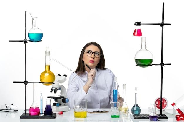 Vista frontale farmacista femminile in tuta medica bianca lavorando e scrivere note pensando su sfondo bianco scienza virus covid- laboratorio pandemico