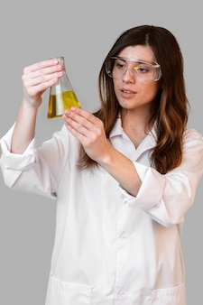 Front view of female chemist with safety glasses holding test tube