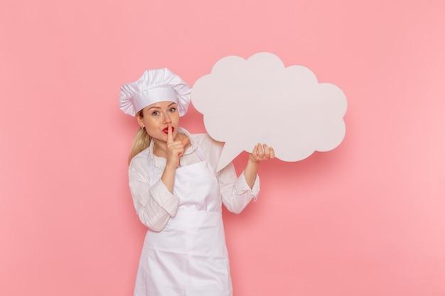 ピンクの壁に大きな白い看板を持っている白い服の正面図女性菓子職人料理人仕事キッチン料理