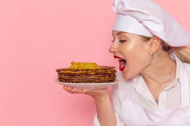 Вид спереди кондитер в белой одежде держит вкусную выпечку на розовом полу кондитерской сладкой выпечки