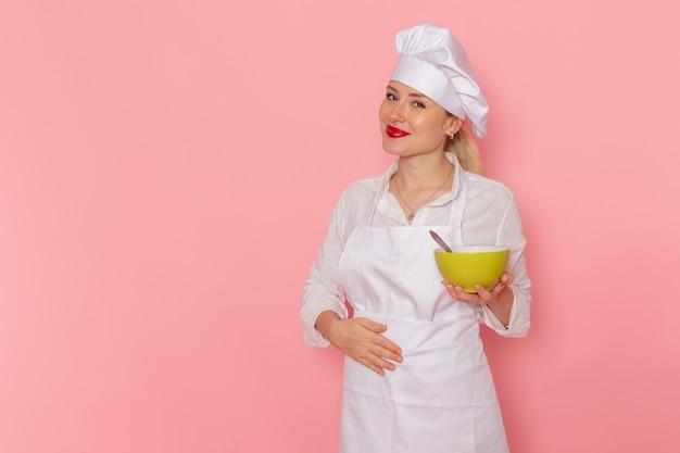 Вид спереди кондитер в белой одежде держит зеленую тарелку с довгой на розовой стене зеленая еда овощной ужин суп