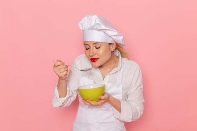 ピンクの壁の食べ物の食事緑の野菜の夕食のスープでそれを味わうdovgaと緑のプレートを保持している白い服の正面図の女性の菓子屋