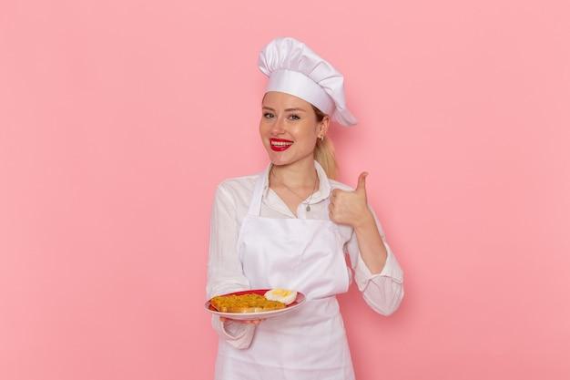 ライトピンクの壁に食べ物が付いている白い摩耗保持プレートの正面図女性菓子職人料理人の仕事キッチン料理料理