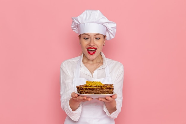 Front view female confectioner in white wear holding delicious pastries on pink wall confectionery sweet pastry work