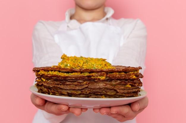 Pasticcere femminile di vista frontale nell'usura bianca che tiene i pasticcini deliziosi sulla pasticceria dolce della pasticceria della parete rosa