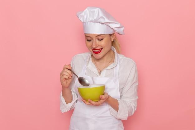 Pasticcere femminile di vista frontale nell'usura bianca che tiene il piatto verde con la colomba sulla zuppa di cena di verdure verdi del pasto del cibo della parete rosa