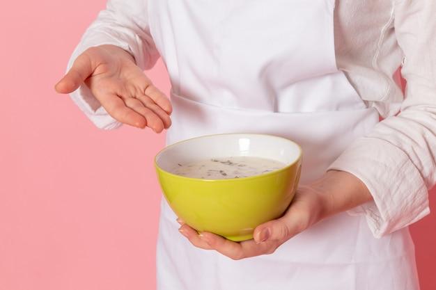 Pasticcere femminile di vista frontale nell'usura bianca che tiene il piatto verde con la colomba sulla verdura dei verdi del pasto dell'alimento della parete rosa