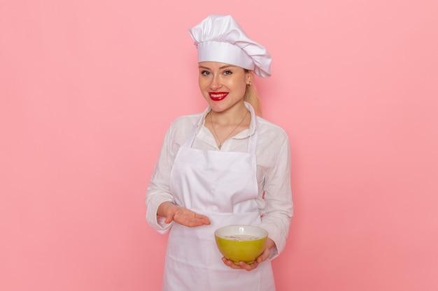 Pasticcere femminile di vista frontale nell'usura bianca che tiene la zolla verde con la colombaia sulla verdura dei verdi della minestra del pasto dell'alimento della parete rosa