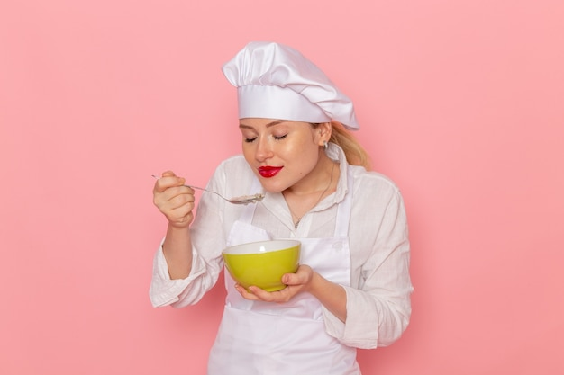 Front view female confectioner in white wear holding green plate with dovga tasting it on the pink wall food meal green vegetable dinner soup