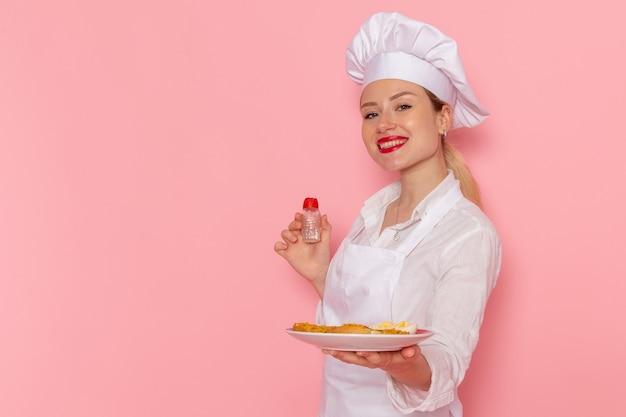 Pasticcere femminile di vista frontale nel piatto della tenuta di usura bianca con il cibo sul cibo della cucina della cucina di lavoro del cuoco della parete rosa