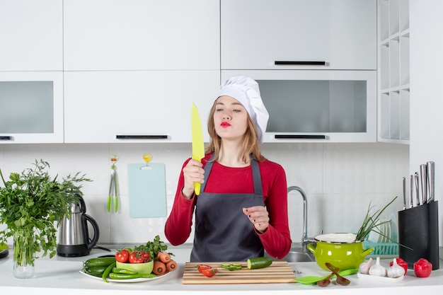 Front view female cook in apron looking at knife in her hand
