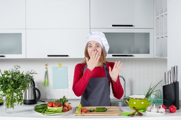 Front view female cook in apron putting hand on her mouth
