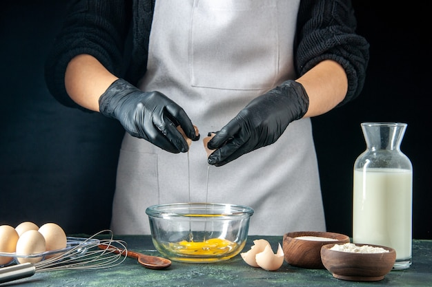 Front view female cook breaking eggs for dough on a dark pastry cake pie bakery worker hotcake cuisine job