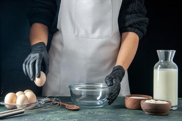 Vista frontale cuoca rompendo le uova per l'impasto sulla pasticceria scura lavoro torta torte panetteria lavoratore cucina