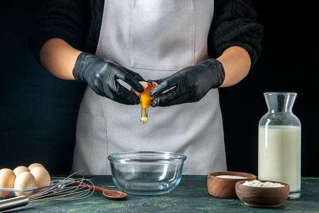 正面図暗いペストリージョブケーキパイベーカリー労働者料理の生地のために卵を壊す女性料理人