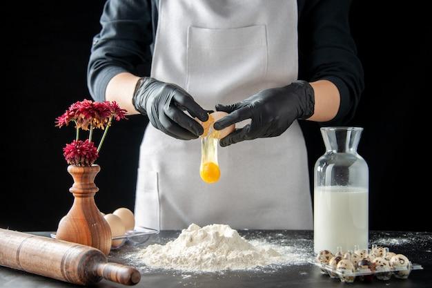 Cuoca vista frontale che rompe le uova in farina su un lavoro scuro pasticceria torta panetteria cottura cuocere torta pasta biscotto