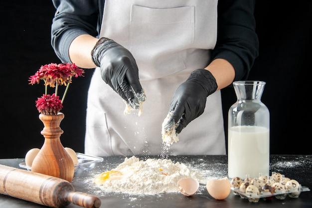 Cuoco femminile di vista frontale che rompe le uova in farina sul lavoro scuro pasticceria torta forno cottura torta pasta biscotto cuocere