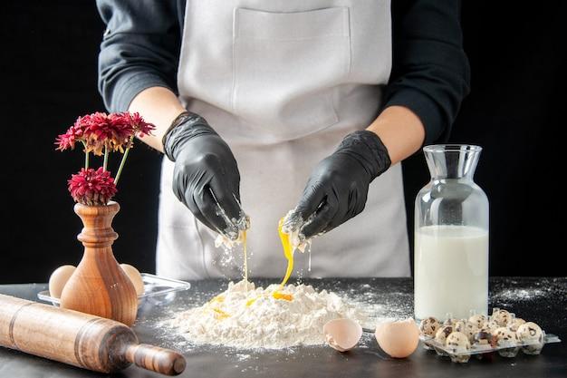 Вид спереди женщина-повар, разбивающая яйца в муку на темной работе, выпечка пирога, выпечки торта, бисквитного теста, выпечки