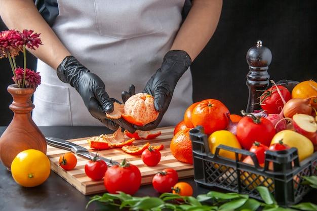 Vista frontale cuoca che pulisce i mandarini sul buio cucina insalata salute dieta pasto vegetale cibo frutta lavoro