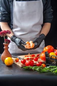 Vista frontale cuoca che pulisce i mandarini su cucina scura insalata salute dieta verdure pasto cibo frutta lavoro